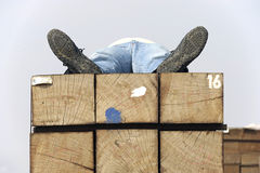 Adult man sleeping on a stack of wood Stock Image
