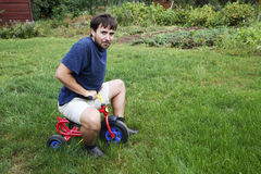 Adult man on a small tricycle. Adult man tying to ride on a small tricycle stock photo