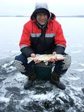 The adult man smiles and shows the freshly caught pike. Winter fishing Stock Images