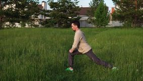 Adult man in sports clothes doing exercises in the park, he listens to music stock video footage