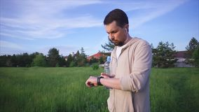 Adult man in a sports suit checks smart watches after physical training stock footage