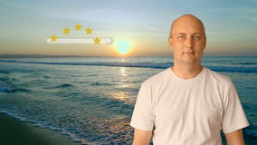 An adult man standing on the beach by the sea at sunset shows an excellent rating for the resort. A high score of 5. Stars for the beach is long and beautiful stock video