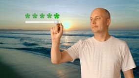 An adult man standing on the beach by the sea at sunset shows an excellent rating for the resort. A high score of 5 Royalty Free Stock Photos
