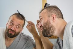 Man using comb in bathroom. Adult man standing in front of the bathroom mirror brushing his short hair using comb. Guy investigating his receding hairline royalty free stock photos
