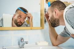 Man using comb in bathroom. Adult man standing in front of the bathroom mirror brushing his short hair using comb. Guy investigating his receding hairline stock photos