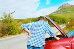 Adult man is standing near his broken car Stock Image