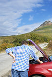 Adult man is standing near his broken car Royalty Free Stock Image