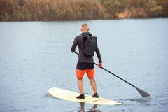 Adult man standing with paddle on paddleboard. Full length portrait of man with backpack engaged rowing on the stand up paddle board in calm river stock photography