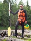 Adult man is standing on stone and holding a helmet and a paddle Stock Image