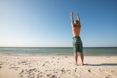 Adult man stretches his arms to the sky while practicing yoga. On the seashore. Back view. Wide angle Stock Photos