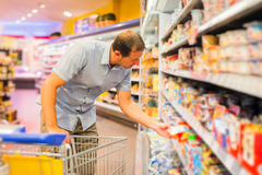 Adult Man At The Supermarket. Adult man buying groceries at the supermarket Royalty Free Stock Image