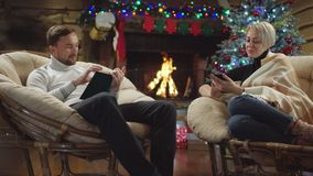 Adult man surfing the Internet on smartphone while woman reading a book in Christmas night. By fireplace and decorated tree stock video