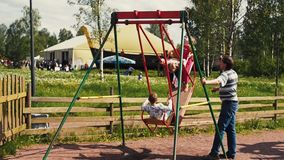 Adult man sway little kids on big swing in summer day. Childhood. Sunny day stock video footage