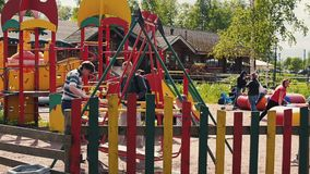 Adult man sway little kids on swing in summer day. Childhood. Playground stock video