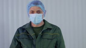 Portrait of worker in uniform removes protective mask from his face. Adult man takes away the protective mask from his face. Worker of factory. Prores codec stock video footage