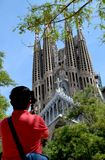 Adult man taking photo of the famous cathedral La Sagrada Familia in Barcelona stock photo