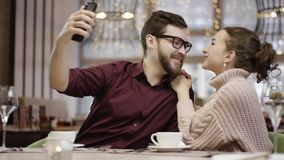 Adult man taking selfie while kissing his girlfriend by restaurant table stock video