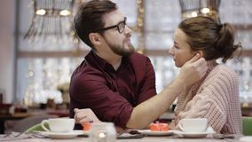 Adult man talks to his girlfriend in a cafe, massages her ear and plays with her nose. Adult man talks to his girlfriend by table in a cafe, massages her ear and stock video footage
