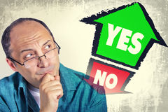 Adult man thinking what to choose between YES and NO Stock Photo