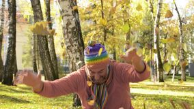 An adult man throws a bunch of yellow fallen leaves in an autumn park.  stock video
