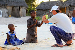 Adult man tourist plays with African children Stock Photos