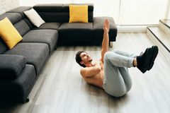 Adult Man Training ABS Muscles At Home Doing One Arm Crunches stock images