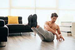 Adult Man Training ABS Muscles At Home Doing Russina Twist Exercise. Fit young white man training at home. Handsome hispanic male athlete working out for stock photography