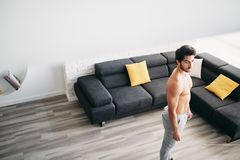 Adult Man Training Muscles At Home Resting Between Exercises royalty free stock image
