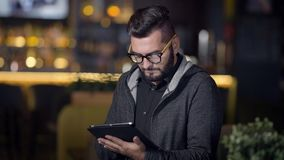 Adult man with trendy hairstyle and glasses on face is surfing internet by tablet sitting in bar in evening. Swiping and typing stock video