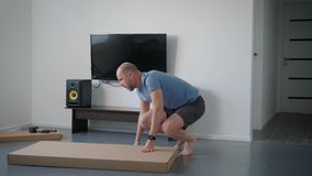 Adult man is turning and lying on a floor big cardboard box in an room of apartment, cutting packing tape. Adult man is turning and lying on a floor big heavy stock video