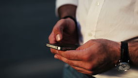 Adult man using black smartphone on street. Watch. Technology. Phone. Tapping stock video footage