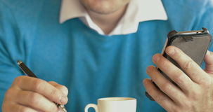 Adult Man Using Smartphone And Drinking Coffee. Close-up of adult man using smartphone and drinking coffee while sitting in cafe stock video