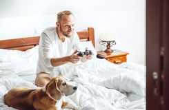 Adult man waked up and plays PC games sitting in bed, his dog wa stock photo