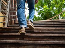 Adult man walking up the wooden stairs. Moving forward concept. royalty free stock image