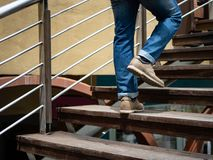 Adult man walking up the wooden stairs. Moving forward Concept. stock photos