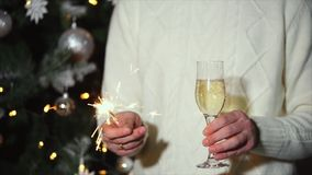 Man is holding sparkler and glass of champagne in party of New year celebration