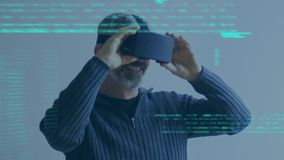 Adult man wearing virtual goggles. Digital composite of an adult Caucasian man wearing virtual goggles while program codes move in the screen stock video footage