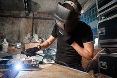 Man  brews a metal. An adult man welder in a black T-shirt and a black welding mask brews a metal welding machine in a dark workshop Royalty Free Stock Image