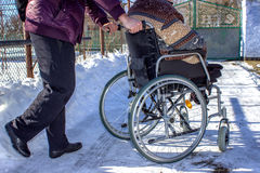Adult man in wheelchair. Close up photo of male hand on wheel Stock Image