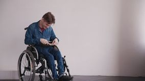 Adult man in wheelchair holding book in hands and sitting. Adult disabled and relaxing man holding book in hands, sitting in comfort wheel chair at room with stock video