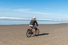 An adult man in a white cap and flip-flops rides his bike through the sand of Cannon Beach, Oregon, USA. royalty free stock photography