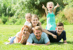 Adult man and woman with four kids lying in park. Adult men and women with four kids lying in park on summer day Stock Image
