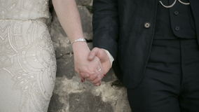 Adult man and woman hold hands on the stone wall background stock video footage