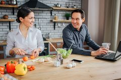 Adult man and woman sit at table in kitchen. She cut vegetables for salad. He work at laptop. They look at each other stock image