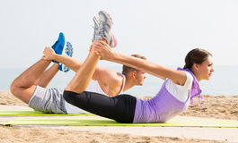 Adult man and woman training on beach by sea Stock Photo