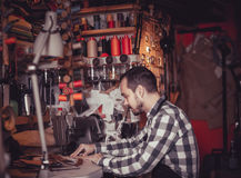 Adult man worker working on stitches for belt. In leather workshop Royalty Free Stock Image
