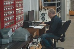 Adult man working at the computer at factory of production CNC machine with lathes. Close up royalty free stock images