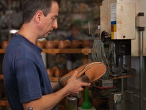 Adult man working in a shoe factory. Checking the quality of the products Royalty Free Stock Photo
