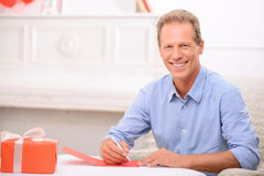 Adult man writing a letter. Romantic valentine. Cheerful overjoyed handsome adult man holding pan and expressing gladness while writing a letter Royalty Free Stock Photo