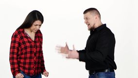 Adult man yells at woman and swings her arm. White. Adult man very screaming at the woman and raises his hand upon her. A woman is silent and very scared, on stock video footage